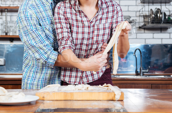Beautiful couple kneading dough and hugging on kitchen Stock photo © deandrobot