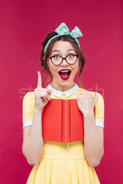 Woman with red book pointing up and having an idea Stock photo © deandrobot
