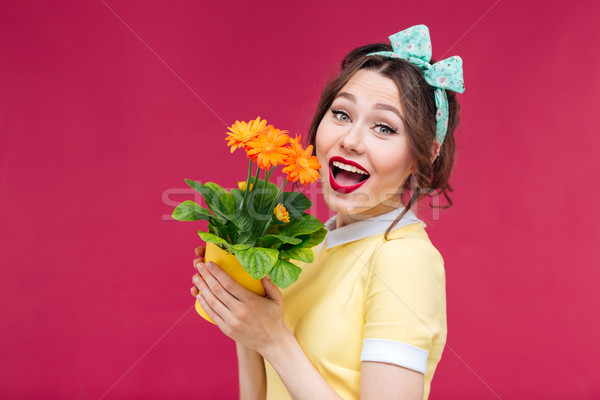 Charming cheerful pinup girl woth orange flower in pot Stock photo © deandrobot