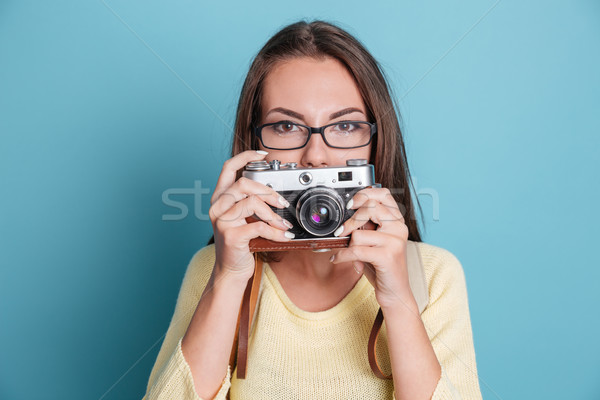 Beautiful woman with photo camera over blue background Stock photo © deandrobot