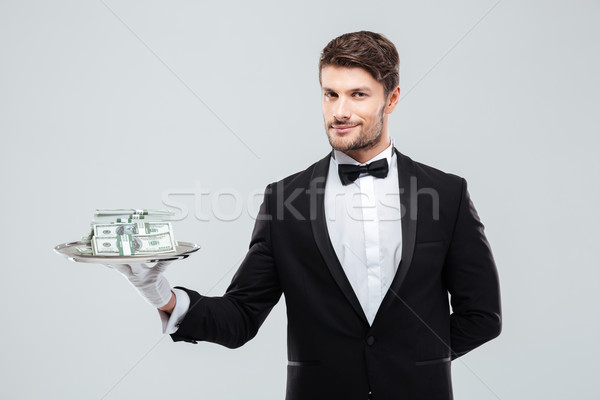 Gorgeous butler in tuxedo standing and holding tray with money Stock photo © deandrobot