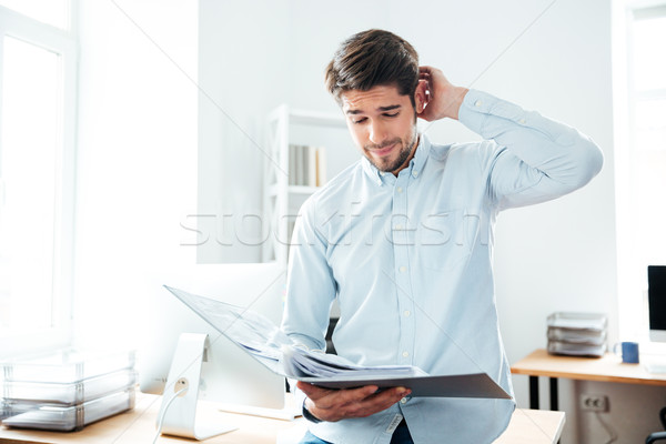 Thoughtful young businessman looking through documents in office Stock photo © deandrobot