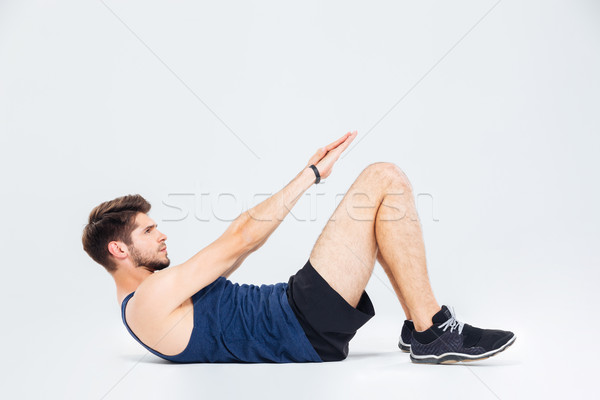 Focused young sportsman training and doing abdominal crunches Stock photo © deandrobot