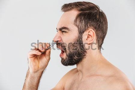 Side view of a man removing nose hair with tweezers Stock photo © deandrobot
