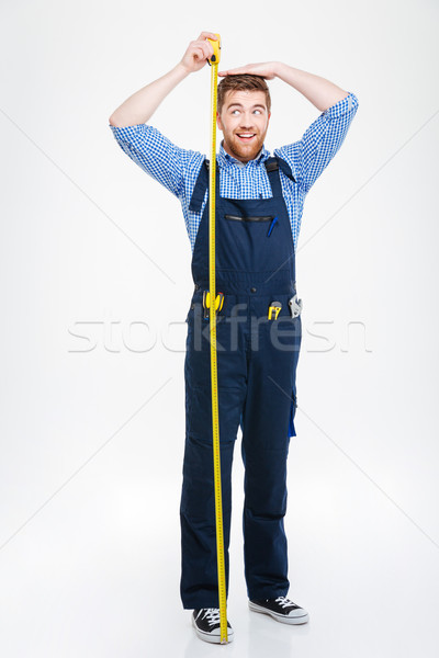 Happy funny young man measuring his body height using tape Stock photo © deandrobot