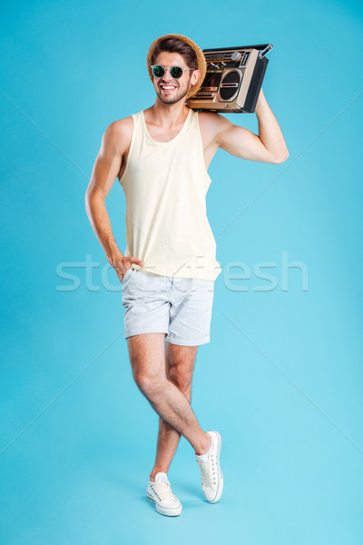 Smiling young man in shorts, hat and sunglasses holding boombox Stock photo © deandrobot