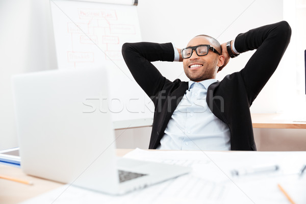 Businessman sitting back in his chair relaxing Stock photo © deandrobot