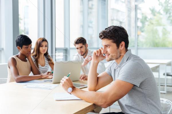 Udany biznesmen mówić komórka spotkanie biznesowe młodych Zdjęcia stock © deandrobot