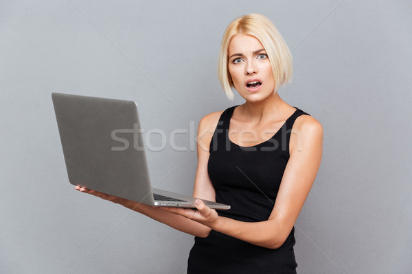 Maravilhado infeliz mulher jovem usando laptop cinza internet Foto stock © deandrobot