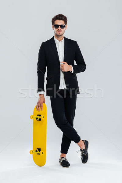 Businessman in sunglaasses leaning on skateboard with legs crossed Stock photo © deandrobot