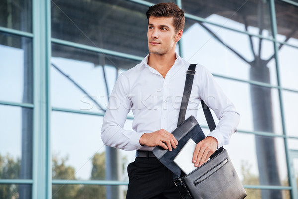 Handsome young businessman taking pc tablet from his bag Stock photo © deandrobot