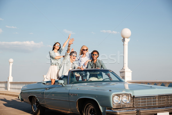 Cheerful young people driving in cabriolet anf having fun Stock photo © deandrobot
