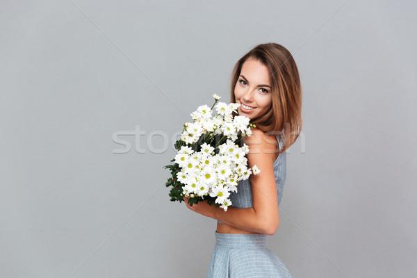 Derűs bájos fiatal nő áll tart virágcsokor Stock fotó © deandrobot