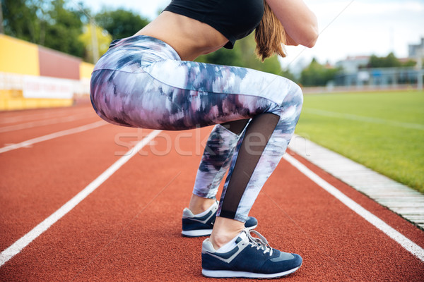 Woman athlete exercising and doing squats on stadium Stock photo © deandrobot