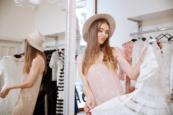 Frowning woman doing shopping and choosing dress in clothing store Stock photo © deandrobot