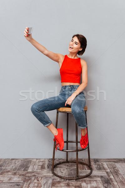 Zdjęcia stock: Uśmiechnięty · młoda · kobieta · Fotografia · smartphone · szary