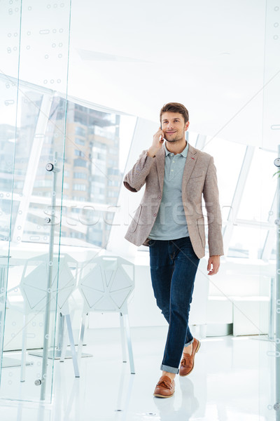 Businessman walking at the office building and talking on phone Stock photo © deandrobot