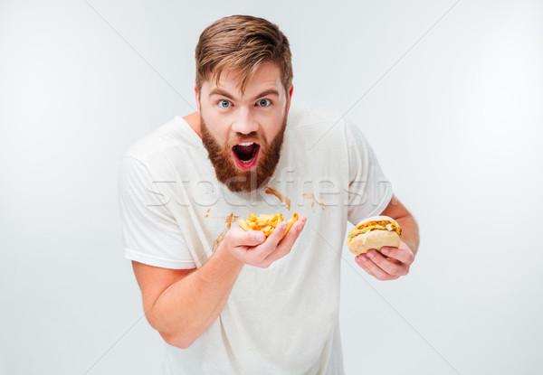 éhes szakállas férfi mocskos póló eszik Stock fotó © deandrobot