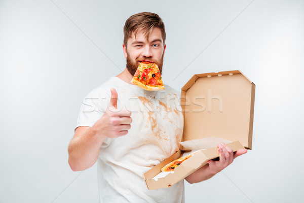Happy hungry man eating pizza and showing thumbs up gesture Stock photo © deandrobot