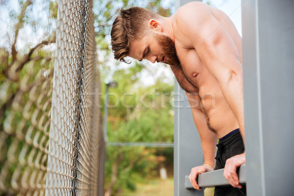 Hnadsome shirtless bearded sportsman doing workout Stock photo © deandrobot
