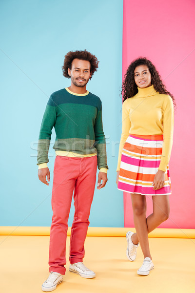 Beautiful african young couple in bright clothes standing and winking Stock photo © deandrobot