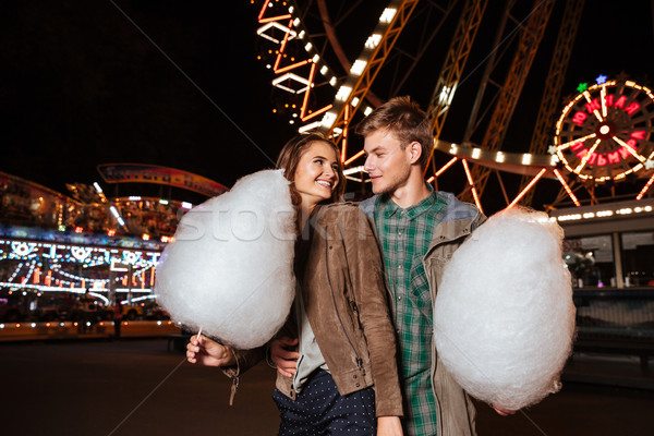 Happy young couple eating cotton candy in amusement park Stock photo © deandrobot