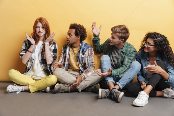Confused redhead girl with her shocked amazed friends sitting Stock photo © deandrobot