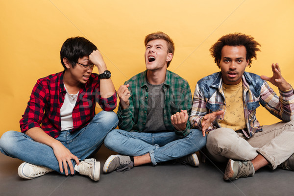 Three mad furious young men friends sitting and shouting Stock photo © deandrobot