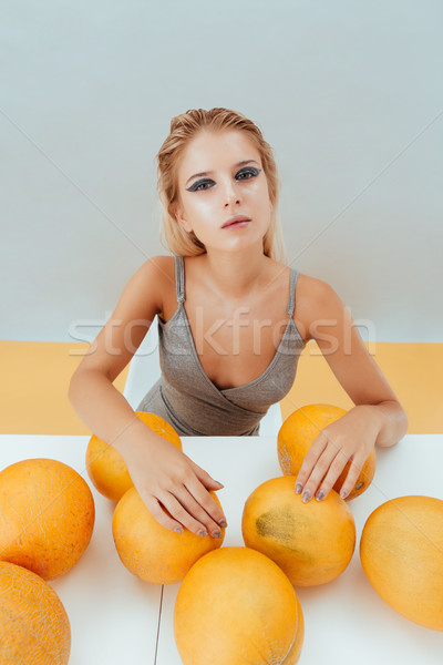 Pretty young woman with fresh yellow melons Stock photo © deandrobot