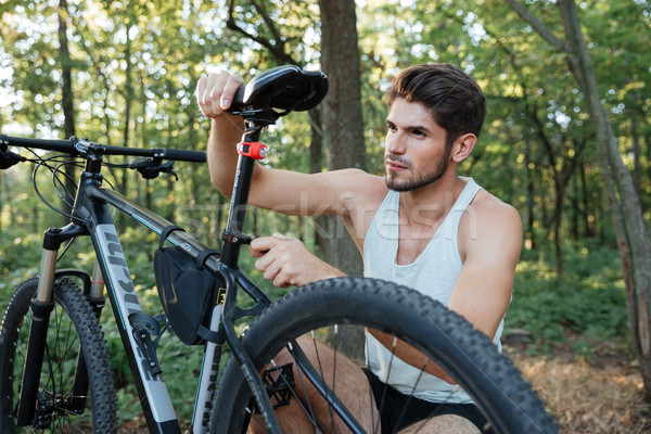 Male mountain biker fixing his bike in the forest Stock photo © deandrobot