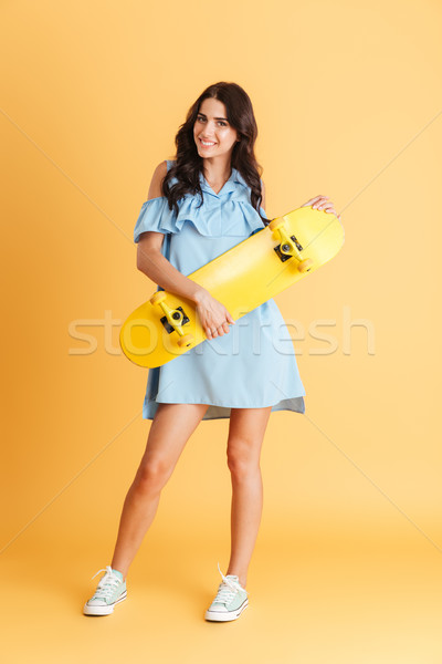 Smiling brunette woman in blue dress holding yellow skateboard Stock photo © deandrobot