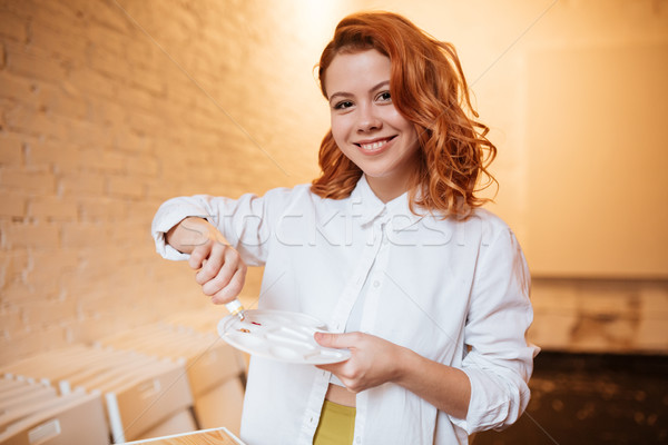Stock photo: Attractive redhead woman painter with oil paints and palette
