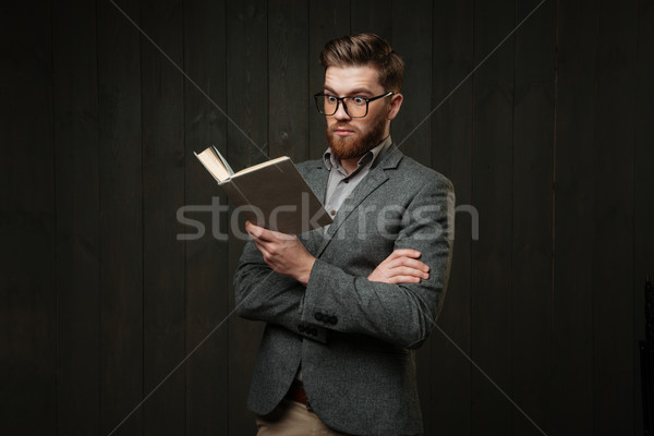 Portrait of amazed casual man in eyeglasses reading book Stock photo © deandrobot