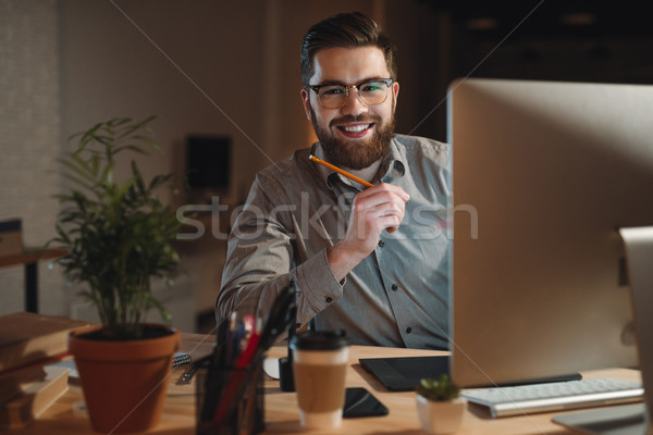 Cheerful bearded designer working at night and looking to camera Stock photo © deandrobot