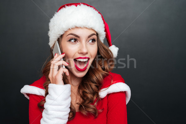 Woman in santa claus costume talking on the cell phone Stock photo © deandrobot