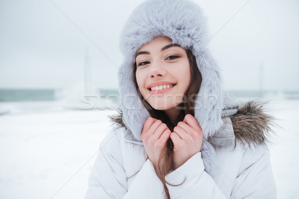 Cheerful young woman wearing hat at cold winter day. Stock photo © deandrobot