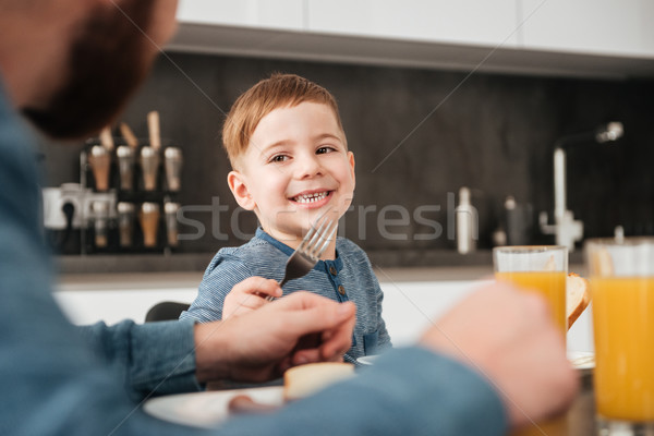 Bearded father eating at kitchen with his little son Stock photo © deandrobot