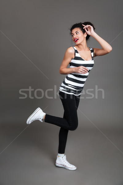 Full length of beautiful african woman running and looking back Stock photo © deandrobot