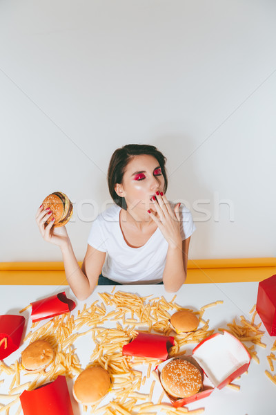 Fatigued bored young woman with hamburger sitting and yawning Stock photo © deandrobot