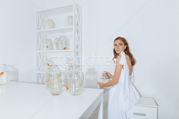 Lovely young woman holding jar with gold fish in room Stock photo © deandrobot