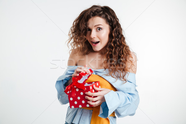 Surprised woman opening a gift box and smiling while standing Stock photo © deandrobot