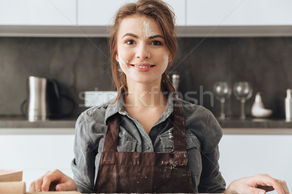 Happy lady standing in kitchen while cooking the dough. Stock photo © deandrobot