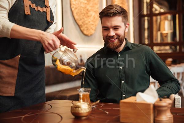 Jovem barbudo homem sessão café olhando Foto stock © deandrobot