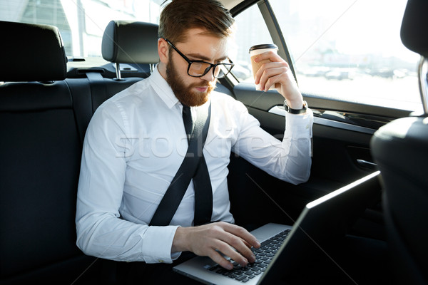 Concentrado hombre de negocios usando la computadora portátil taza café Foto stock © deandrobot