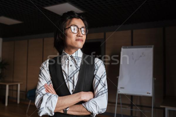 Atractivo jóvenes Asia hombre pie los brazos cruzados Foto stock © deandrobot