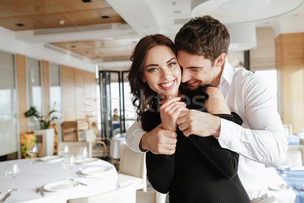 Stock photo: Loving happy couple hugging in restaurant indoors
