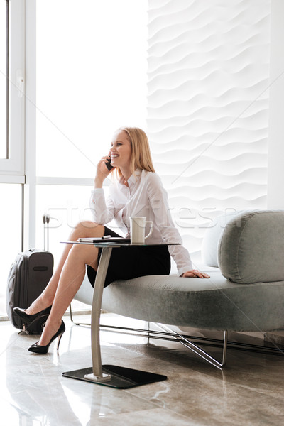 Happy business woman sitting in office while talking by phone Stock photo © deandrobot