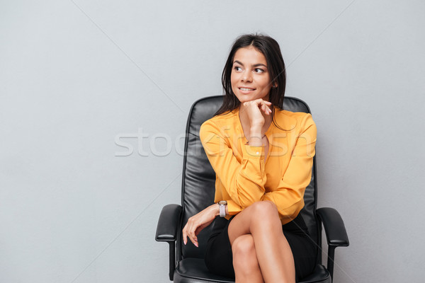 Stock photo: Thoughtful business woman sitting in chair and looking away