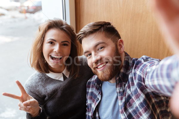 Cheerful young couple taking selfie photo indoors at the window Stock photo © deandrobot