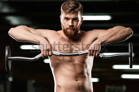 Cheerful sports man make sport exercises with barbell Stock photo © deandrobot